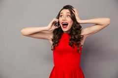 Happy amazed woman in red dress talking on the phone Royalty Free Stock Photos