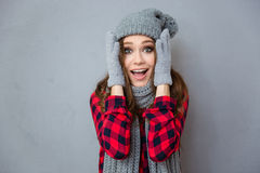 Happy amazed woman in winter cloth. Portrait of a happy amazed woman in winter cloth looking at camera over gray background Stock Photos