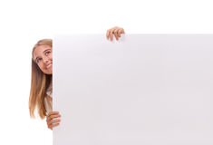 Happy amazed young girl is popping out from the side of white blank banner,isolated Stock Images