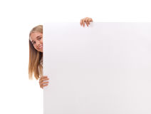 Happy amazed young girl is popping out from the side of white blank banner,isolated Royalty Free Stock Images