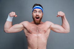 Happy amazed young sportsman standing and showing biceps Royalty Free Stock Image