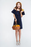 Happy amazed young woman standing and holding basket with fruits Royalty Free Stock Image