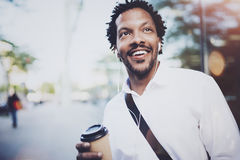 Happy American African man in headphone walking at sunny city with take away coffee and enjoying to listen to music on Royalty Free Stock Photo