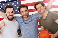 Happy american basketball fans cheering over flag. Picture of happy male friends cheering and watching sports on tv Stock Photos