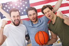 Happy american basketball fans cheering over flag. Picture of happy male friends cheering and watching sports on tv Royalty Free Stock Photos