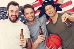 Happy american basketball fans cheering over flag. Picture of happy male friends cheering and watching sports on tv Royalty Free Stock Image
