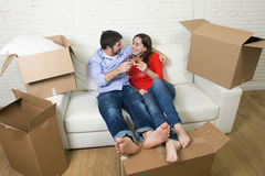 Happy American couple lying on couch together celebrating moving in new house flat or apartment Stock Images