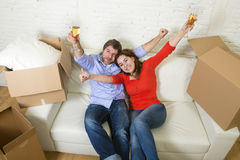 Happy American couple lying on couch together celebrating moving in new house flat or apartment Stock Photos
