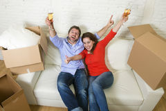 Happy American couple lying on couch together celebrating moving in new house flat or apartment Stock Photo