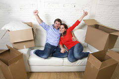 Happy American couple lying on couch together celebrating moving in new house flat or apartment Royalty Free Stock Image