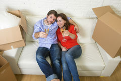 Happy American couple lying on couch together celebrating moving in new house flat or apartment Stock Photography