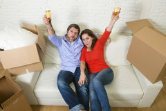 Happy American couple lying on couch together celebrating moving in new house flat or apartment Royalty Free Stock Photos