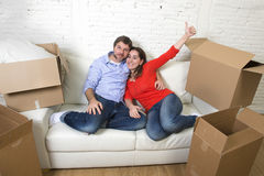 Happy American couple lying on couch together celebrating moving Royalty Free Stock Photo
