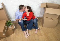 Happy American couple sitting on floor kissing celebrating moving in new house flat or apartment Royalty Free Stock Photos