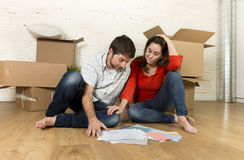Happy American couple sitting on floor moving in new house looking blueprints Royalty Free Stock Photos