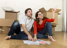 Happy American couple sitting on floor moving in new house looking blueprints Stock Photo