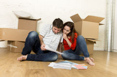 Happy American couple sitting on floor moving in new house looking blueprints Royalty Free Stock Photography