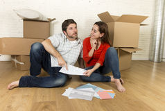 happy American couple sitting on floor moving in new house looking blueprints Stock Images