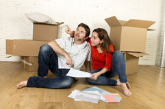 Happy American couple sitting on floor moving in new house looking blueprints Stock Image