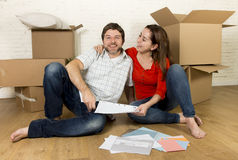 Happy American couple sitting on floor moving in new house looking blueprints Royalty Free Stock Photo