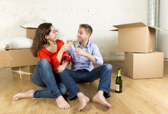 Happy American couple sitting on floor unpacking together celebrating with champagne toast moving in a new house Stock Photo