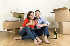 Happy American couple sitting on floor unpacking together celebrating with champagne toast moving in a new house Stock Images