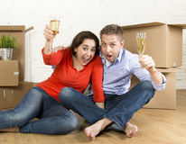Happy American couple sitting on floor unpacking together celebrating with champagne toast moving in a new house Stock Photos