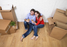 Happy American couple sitting on floor unpacking together celebrating moving to new house flat or apartment Royalty Free Stock Photography