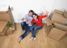 Happy American couple sitting on floor unpacking together celebrating moving to new house flat or apartment Royalty Free Stock Photo