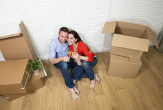 Happy American couple sitting on floor unpacking together celebrating moving to new house flat or apartment Stock Photography
