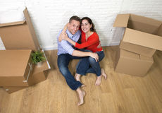 Happy American couple sitting on floor unpacking together celebrating moving to new house flat or apartment Stock Photos