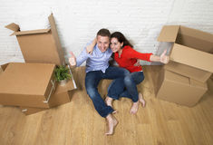Happy American couple sitting on floor unpacking together celebrating moving to new house flat or apartment Stock Images