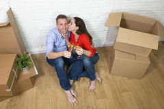 Happy American couple sitting on floor unpacking together celebrating moving to new house flat or apartment Royalty Free Stock Photos
