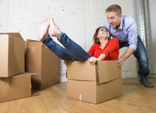 Happy American couple unpacking moving in new house playing with unpacked cardboard boxes Royalty Free Stock Photos
