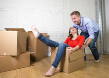 Happy American couple unpacking moving in new house playing with unpacked cardboard boxes Stock Photography