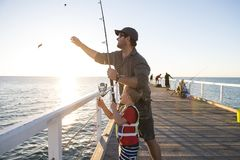 Father teaching little young son to be a fisherman, fishing together on sea dock embankment enjoying and learning using the fish r stock images