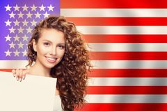 Happy American Girl With White Paper Against The USA Flag Background. Travel And Learn English Language Concept Royalty Free Stock Images