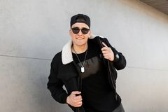 Happy american young hipster man in dark sunglasses in stylish black jacket in a cap in a trendy t-shirt with an amulet poses. And smiles near a modern building stock images