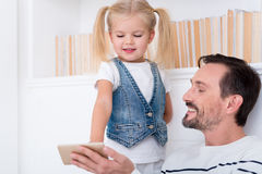 Happy amused father and daughter looking at the screen. Something interesting. Nice positive delighted daughter and father looking at the screen of a cell phone royalty free stock photo