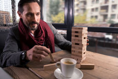 Happy amused man holding a wooden block. Jenga game. Handsome amused cheerful man sitting at the table and holding a wooden block while playing the board game Royalty Free Stock Image