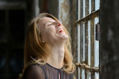 Happy amused young woman enjoying a good laugh. With her head thrown back and closed eyes in front of a large rustic window indoors royalty free stock images