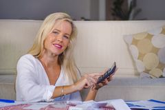 Happy And Beautiful Blond Caucasian Woman Smiling Relaxed Calculating Successful Domestic Money Income And Financial Monthly Busin Stock Photography