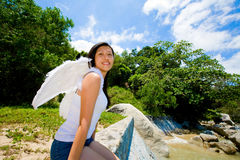 Happy angel. Woman sitting on the edge by the sea Royalty Free Stock Photo