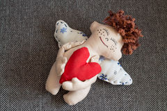 Happy Angel. Happy Angel hugging red heart. Soft toy Royalty Free Stock Image