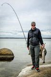 Happy angler with fishing trophy Stock Images