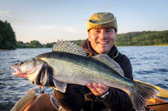 Happy angler with fresh caught big walleye. Happy angler with trophy fish in summer season stock image