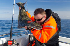 Happy angler give a kiss to halibut fishing trophy. Sea fishing adventures for a young men stock image
