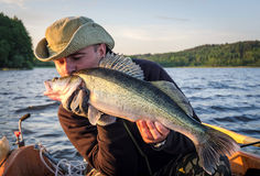 Happy angler kissing walleye fishing trophy Royalty Free Stock Images