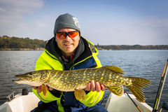 Happy angler with october's pike fishing trophy Royalty Free Stock Images