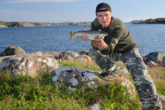 Happy Angler With Sea Trout Royalty Free Stock Photo